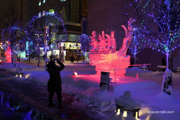 japanese tourist takes a photo of ice art
